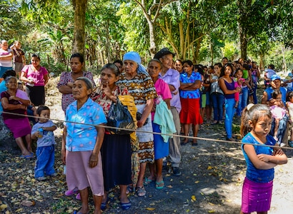 Villagers from Laguna, Honduras, line up to receive bags of goods from members of Joint Task Force-Bravo, Feb. 28, 2015.   As part of the 59th Chapel Hike, more than 172 members assigned to Joint Task Force-Bravo laced up their hiking boots and completed a seven-mile round trip hike to deliver over 4,500-pounds of donated try goods to villagers in need. (U.S. Air Force photo/Tech. Sgt. Heather Redman)