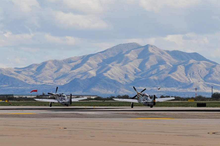 Two P-51 Mustangs taxi down the flightline during the 2015 Heritage Flight Training and Certification Course at Davis-Monthan Air Force Base, Ariz., Feb. 28, 2015. During the course, aircrews practiced ground and flight training to enable civilian pilots of historic military aircraft and U.S. Air Force pilots of current fighter aircraft to fly safely in formations together. (U.S. Air Force photo by Airman 1st Class Chris Drzazgowski/Released)