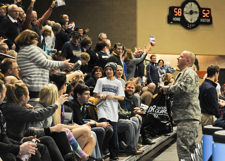 SIOUX FALLS, S.D. - Master Sgt. Carl Dellman, 114th Communications specialist, throws water bottles, lanyards, flash drives, and basketballs to the crowd in Sioux Falls, S.D., March 1, 2015. Dellman was there to participate in military appreciation day at the Northern Sun Intercollegiate Conference NCAA II basketball tournament.(National Guard photo by Staff Sgt. Luke Olson/Released)