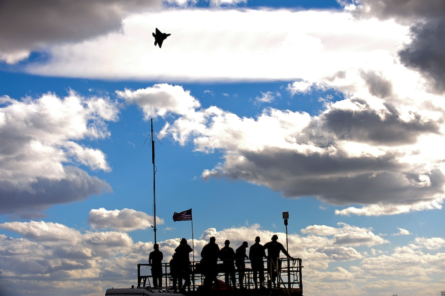 A U.S. Air Force F-22 Raptor flies above spectators during the 2015 Heritage Flight Training and Certification Course at Davis-Monthan Air Force Base, Ariz., Feb. 28, 2015. The annual aerial demonstration training event has been held at D-M since 2001, providing civilian and military pilots the opportunity to practice flying in formation together for the upcoming air show season. (U.S. Air Force photo by Airman 1st Class Chris Drzazgowski/Released)