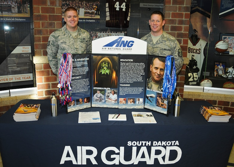 SIOUX FALLS, S.D. - Master Sgt. Eric Tidemann and Tech. Sgt. Bo Martz, 114th Force Support Squadron recruiters, stand post at their booth during military appreciation day at the Northern Sun Intercollegiate Conference NCAA II basketball tournament in Sioux Falls, S.D., March 1, 2015. The pair gave away lanyards, water bottles, flash drives, and basketballs to kids and fans at the event.(National Guard photo by Staff Sgt. Luke Olson/Released)