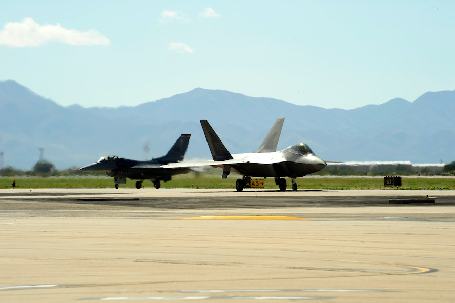 A F-22 Raptor and a F-16 Fighting Falcon taxi back to their parking spot after practicing an aerial demonstration during the 2015 Heritage Flight Training and Certification Course at Davis-Monthan Air Force Base, Ariz., March 1, 2015. The annual aerial demonstration training event has been held at D-M since 2001, providing civilian and military pilots the opportunity to practice flying in formation for the upcoming air show season. (U.S. Air Force photo by Tech. Sgt. Courtney Richardson/Released)
