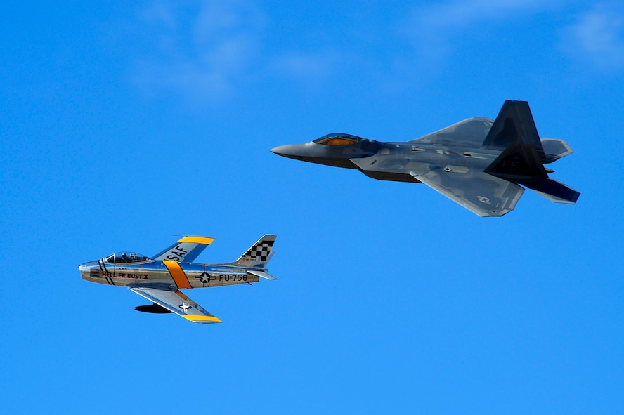 A F-86 Sabre and F-22 Raptor practice flying their aerial demonstration during the 2015 Heritage Flight Training and Certification Course at Davis-Monthan Air Force Base, Ariz., Feb. 28, 2015. The annual aerial demonstration training event has been held at D-M since 2001, providing civilian and military pilots the opportunity to practice flying in formation for the upcoming air show season. (U.S. Air Force photo by Staff Sgt. Courtney Richardson/Released)