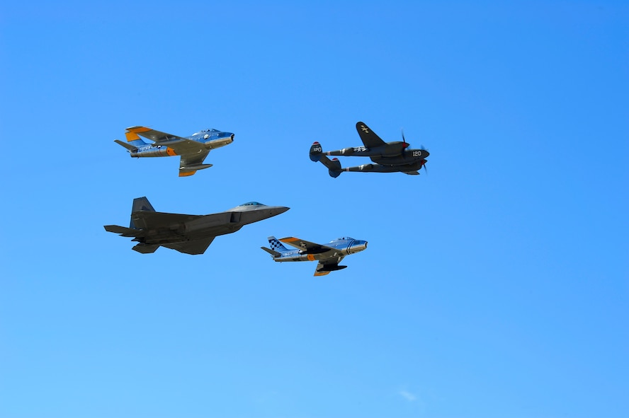 A P-38 Lightning, two F-86 Sabres and a F-22 Raptor fly in formation together during the 2015 Heritage Flight Training and Certification Course at Davis-Monthan Air Force Base, Ariz., Feb. 28, 2015. During the course, aircrews practiced ground and flight training to enable civilian pilots of historic military aircraft and U.S. Air Force pilots of current fighter aircraft to fly safely in formations together. (U.S. Air Force photo by Staff Sgt. Courtney Richardson/Released)