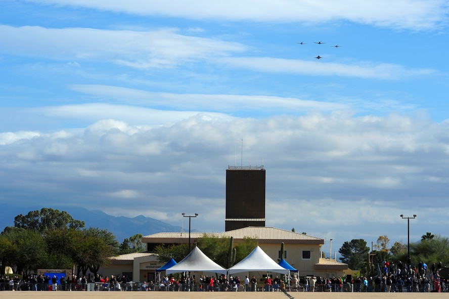 Spectators watch as a P-47 Thunderbolt, two P-51 Mustangs, and a F-16 Fighting Falcon fly in formation overhead during the 2015 Heritage Flight Training and Certification Course at Davis-Monthan Air Force Base, Ariz., Feb. 28, 2015. During the course, aircrews practiced ground and flight training to enable civilian pilots of historic military aircraft and U.S. Air Force pilots of current fighter aircraft to fly safely in formations together. (U.S. Air Force photo by Staff Sgt. Courtney Richardson/Released)