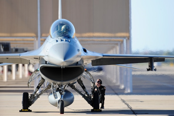An F-16 Fighting Falcon pilot and crew chief communicate while preparing for a flight during the 2015 Heritage Flight Training and Certification Course at Davis-Monthan Air Force Base, Ariz., Feb. 27, 2015.  During the course, aircrews practiced ground and flight training to enable civilian pilots of historic military aircraft and U.S. Air Force pilots of current fighter aircraft to fly safely in formations together. (U.S. Air Force photo by Airman 1st Class Chris Massey/Released)