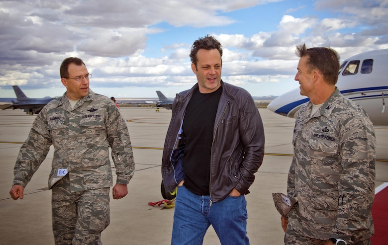 """Actor and USO volunteer Vince Vaughn (center) is greeted by Col. Eric Leshinsky (right) and Col. David Radomski Feb. 28, 2015, on the flight line at Edwards Air Force Base, Calif. Vaughn treated troops and their families to an advance screening of his upcoming film, """"Unfinished Business,"""" during his USO visit to the base. Leshinsky is the commander of 412th Mission Support Group and Radomski is the vice commander of the 412th Test Wing. (USO photo/Dave Gatley)"""