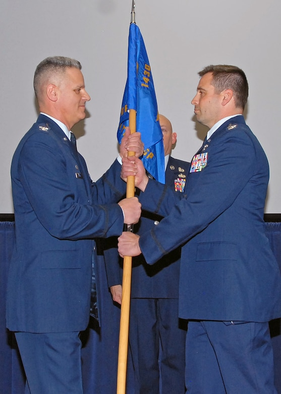 Colonel John Sullivan (right) relinquishes command of the 143d Airlift Wing Operations Group by passing the guidon to Colonel Arthur Floru, Commander, 143d AW at a ceremony held at Quonset Air National Guard Base, North Kingstown, Rhode Island on February 8, 2015. National Guard Photo by Technical Sgt Jason Long (RELEASED)