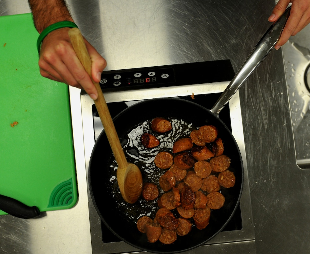 Andouille sausage cooks in a skillet before being added to a roux made of butter, onions, bell peppers, celery and garlic during a gumbo cooking class held by the 81st Force Support Squadron's Single Airman Program Feb. 26, 2015, at the Mississippi Gulf Coast Community College, Perkinston, Miss. Traditionally served with andouille sausage and shrimp, gumbo's versatility allows almost any meat to be added or substituted to the stew. (U.S. Air Force photo by Airman 1st Class Duncan McElroy)