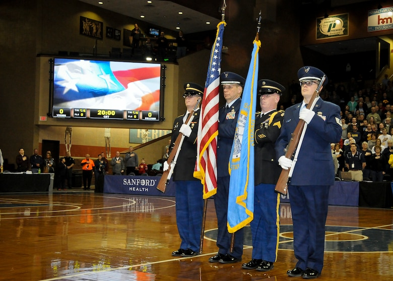 SIOUX FALLS, S.D. - Members of the South Dakota Air and Army National Guard posts the colors during the national anthem at the Northern Sun Intercollegiate Conference NCAA II basketball tournament in Sioux Falls, S.D., March 1, 2015.  (National Guard photo by Staff Sgt. Luke Olson/Released)