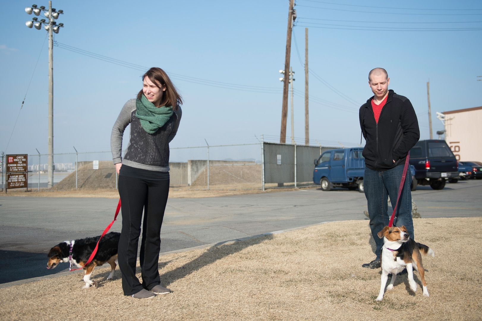Army Sgt. Stephen Adams and his wife Elena walk their dogs for the first time after in processing the Osan Air Base passenger terminal, Republic of Korea, March 2, 2015. Sergeant Adams arrived on the Peninsula that day to join the 2nd Battalion, 2nd Aviation Regiment, 2nd Infantry Division at Camp Humphreys, Republic of Korea, as a UH-60 Black Hawk helicopter crew chief. (U.S. Air Force photo by Staff Sgt. Shawn Nickel/Released)