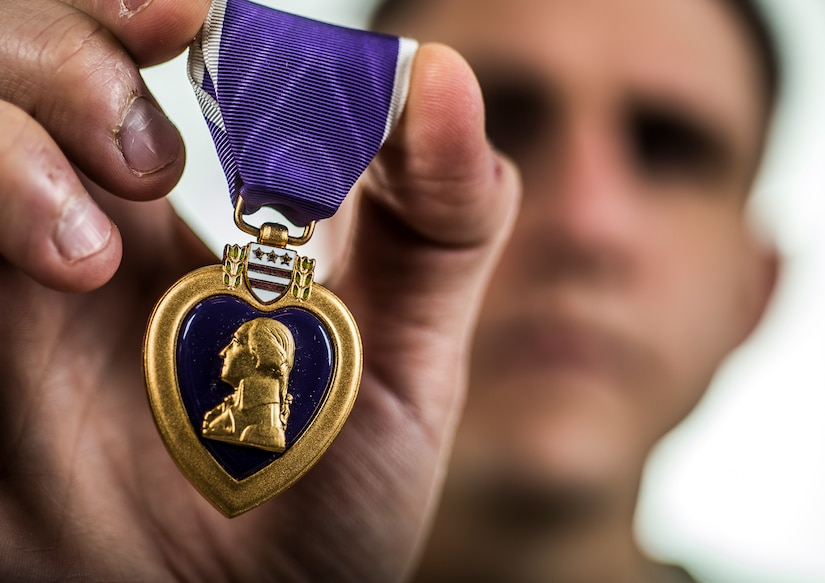 An airman holds up his Purple Heart medal.