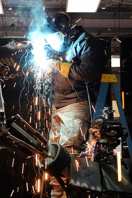 "Tech. Sgt. Patrick Pittman, 386th Expeditionary Maintenance Squadron Combat Metals Flight machinist, puts the finishing welds on his scrap metal sculpture. Dubbed ""Ironman"" by it's creators, the project utilized more than 200 pieces of scrap metal collected by a volunteer crew of four, and it took two weeks to assemble. (U.S. Air Force photo by Master Sgt. Eric Petosky)"