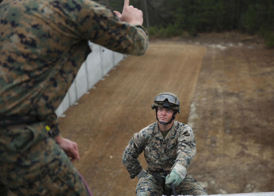 Corporal Carl Adams, a Weapons Company squad leader with 2nd Battalion, 6th Marine Regiment and native of Bellefontaine, Ohio, waits for the go-ahead to descend the rapel tower during the Helicopter Ropes Suspension Techniques course taught by Expeditionary Operations Training Group March 3, 2015, at Stone Bay aboard Marine Corps Base Camp Lejeune, N.C. The 10-day course teaches Marines to become subject-matter experts at controlling fast-rope or rapelling exercises and units with HRST capabilities make it possible to insert or extract Marines from an area where landing an aircraft would be impractical. (Marine Corps photo by Cpl. Michelle Reif/released)