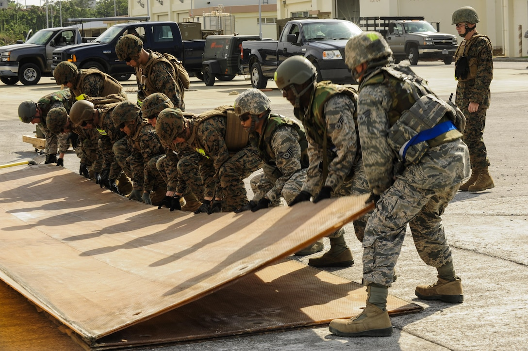 Airmen from the 18th Civil Engineer Group and 172nd and 171st Engineering Company Marines unfold a fiber glass mat during a joint airfield damage and repair contingency exercise Feb. 26, 2015, at Kadena Air Base, Japan. The Airmen and Marines worked together in order to repair a 50-foot crater on a mock runway. (U.S. Air Force photo/Airman 1st Class John Linzmeier)