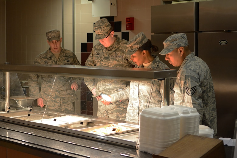 Tech. Sgt. Andrew Combs, 115th Force Support Squadron, brainstorms with the active-duty Airmen from Mildenhall Air Force Base, England, in the Mildenhall dining facility Feb. 19, 2015. The boilers went out on the serving line, so they were forced to develop a plan to keep the food warm. The 115 FW Airmen integrated themselves and trained alongside active-duty forces overseas for two weeks. (U.S. Air National Guard photo by Senior Airman Andrea F. Rhode)