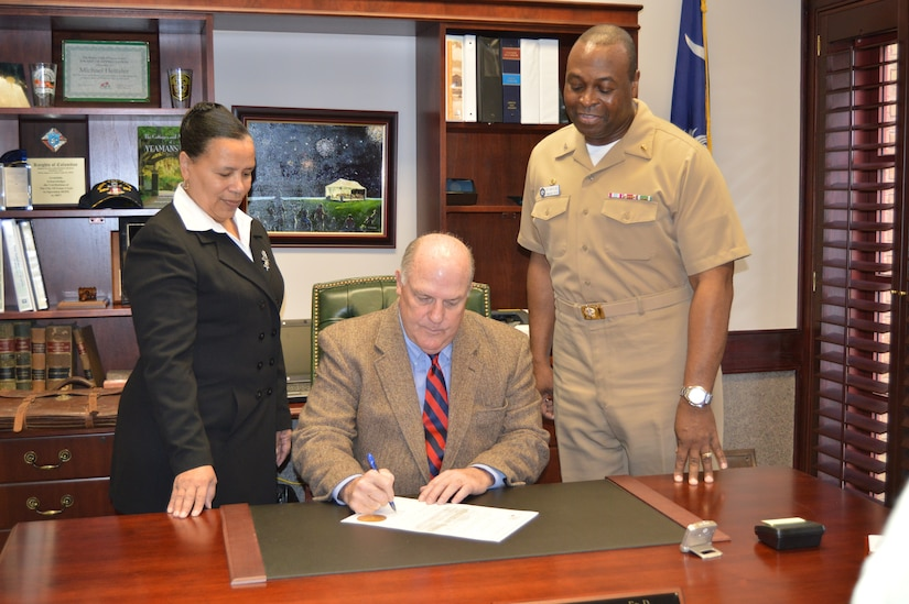 Goose Creek Mayor Michael Heitzler, center, with Capt. Marvin Jones, Naval Health Clinic Charleston commanding officer, right, and Ruth Warren-Goldston, NHCC Patient Safety officer, signs a proclamation March 2, 2015 designating March 8 to 14 Patient Safety Awareness Week in his office at Goose Creek City Hall. Patient Safety Awareness Week is an annual education and awareness campaign for healthcare safety led by the National Patient Safety Foundation. Each year, NHCC joins healthcare organizations from around the globe to participate in educational events that empower hospital staff and patients to eliminate preventable patient harm and provide the highest quality of care for patients. (Navy photo/Kris Patterson)