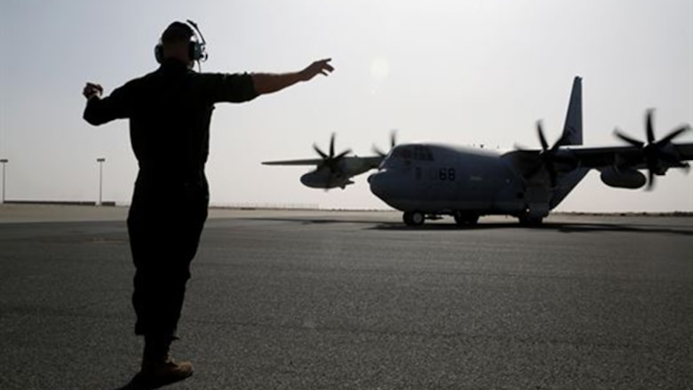 A U.S. Marine with Marine Aerial Refueler Transport Squadron 352, Special Purpose Marine Air Ground Task Force – Crisis Response – Central Command, directs a KC-130J Hercules aircraft to the runway before takeoff in the Central Command area of operations, Feb. 23, 2015. The Marines, sailors and aircraft with VMGR 352 support SPMAGTF – CR – CC by transporting supplies, equipment and personnel to various locations in the region.