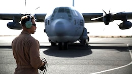A U.S. Marine aircraft crewman with Marine Aerial Refueler Transport Squadron 352, Special Purpose Marine Air Ground Task Force – Crisis Response – Central Command, performs pre-flight checks on a KC-130J Hercules aircraft before takeoff in the Central Command area of operations, Feb. 23, 2015. The Marines, sailors and aircraft with VMGR 352 support SPMAGTF – CR – CC by transporting supplies, equipment, and personnel to various locations in the region.