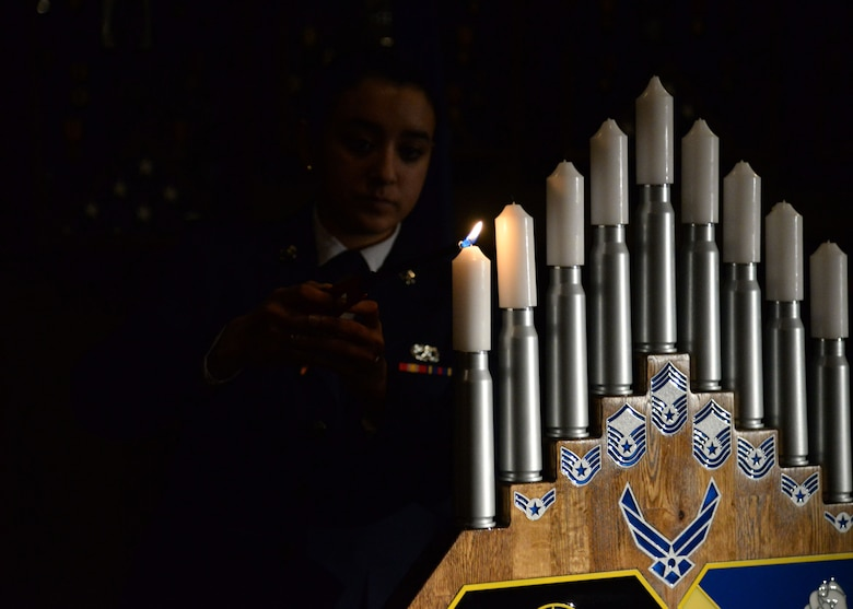 A U.S. Air Force airman basic lights a candle during the candle ceremony at the Chief Master Sergeant Recognition Ceremony, March 4, 2015 at Cannon Air Force Base, N.M. Promotion to the rank of chief master sergeant is said to be the pinnacle of one's enlisted military career, and arguably one of the most significant achievements in such a professional's life. (U.S. Air Force photo/Staff Sgt. Alexxis Mercer)