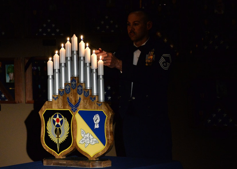 A U.S. Air Force senior master sergeant lights the eighth candle during the candle ceremony at the Chief Master Sergeant Recognition Ceremony, March 4, 2015 at Cannon Air Force Base, N.M. The Career Compensation Act of 1958 allowed Congress to limit the Air Force in promoting two percent of the enlisted force to the grade of senior master sergeant and one percent to the grade of chief master sergeant. (U.S. Air Force photo/Staff Sgt. Alexxis Mercer)