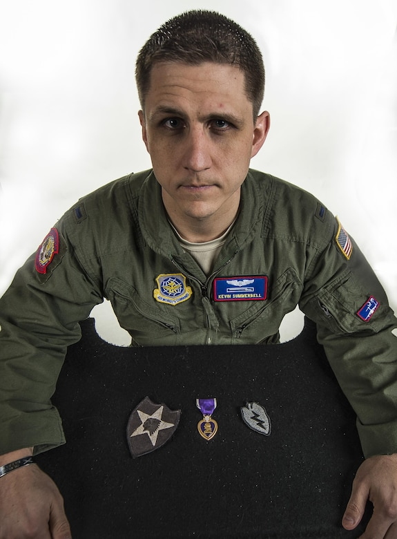 First Lt. Kevin Summerbell shows his Purple Heart and Army patches he kept from serving in the Army, Feb. 19, 2015, at Joint Base Charleston, S.C. Summerbell later attended ROTC and commissioned as an officer in the Air Force to be a C-17 Globemaster III pilot, the same aircraft he was flown back on after being wounded in combat. He is now assigned to the 15th Airlift Squadron at Charleston. (U.S. Air Force photo/Senior Airman Dennis Sloan)