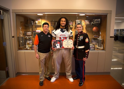 Sgt. Daniel Pluth (right), a Marine recruiter in Tacoma, Washington, presents a Semper Fidelis All-American Bowl certificate to Benning Potoae (center), a senior at Lakes High School in Lakewood, Washington, together with Lakes football coach Dave Miller March 3, 2015. Potoae, a highly-touted defensive end from Dupont, Washington, was one of three Washington State football players selected to play in the Jan. 4 game in Carson, California. Following his high school graduation, Potoae will attend the University of Washington on a football scholarship. (U.S. Marine Corps photo by Sgt. Reece Lodder)