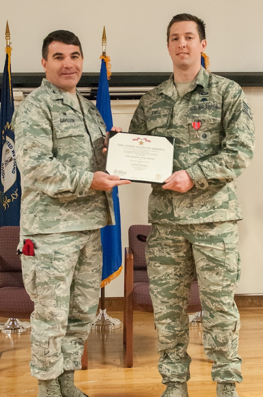 Col. Matthew Davidson (left), commander of the 24th Special Operations Wing, presents Staff Sgt. Nicholas P. Jewell, a combat controller in the Kentucky Air National Guard's 123rd Special Tactics Squadron, with the Bronze Star Medal during a ceremony Feb. 7, 2015, at the Kentucky Air National Guard Base in Louisville, Ky. Jewell earned the award for meritorious achievement while supporting Operation Enduring Freedom in Afghanistan in 2014. (U.S. Air National Guard photo by Staff Sgt. Vicky Spesard)