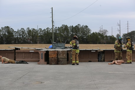 Firefighters evaluate the scene of a simulated vehicle borne IED near Cunningham Gate during the 2015 Crisis Response Drill at Marine Corps Air Station Cherry Point, N.C., March 3, 2015.  The annual exercise was designed to test Cherry Point's emergency preparedness program and response procedures.