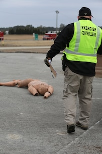 An exercise controller with the Marine Corps Regional Exercise Team East approaches a staged victim prior to the start of the 2015 Crisis Response Drill at Marine Corps Air Station Cherry Point, N.C., March 3, 2015.  The annual exercise is designed to test Cherry Point's emergency preparedness program and response procedures.