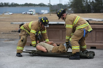Raymond Bane, left, and Joseph Smith lay a casualty on a stretcher following a simulated vehicle borne IED during the 2015 Crisis Response Drill at Marine Corps Air Station Cherry Point, N.C., March 3, 2015.  The annual exercise was designed to test Cherry Point's emergency preparedness program and response procedures. Bane and Smith are firefighters with Cherry Point's Fire and Emergency Services Department.