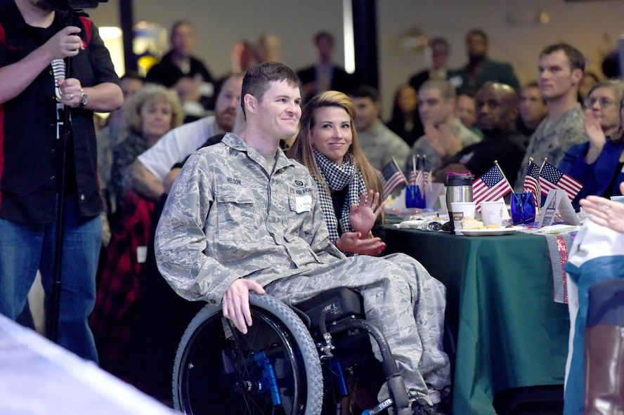Building Homes for Heroes officials surprise Air Force Special Operations Command Air Commando 1st Lt. Nate Nelson and his wife with a new mortgage-free home during a Fort Walton Beach Chamber of Commerce breakfast, March 6, 2015. While deployed to a forward operating location in Afghanistan in 2013, Nelson was injured when an enemy rocket impacted the building wall he was sleeping against.(Courtesy photo by Nick Tomecek/Northwest Florida Daily News)