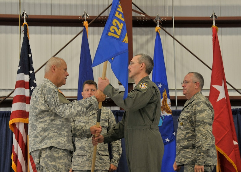 Col. Patrick R. Renwick (center), newly appointed Commander of the 122nd Fighter Wing, Fort Wayne Air National Guard Base, Fort Wayne,  Indiana, hands the wing guidon to Maj. Gen. R. Martin Umbarger (left), the Adjutant General of Indiana, as he assumes command of the wing following the retirement of former wing commander Col. David L. Augustine (right), Sep. 13, 2014. Augustine served as 122FW Commander for over three years. Renwick arrived from the 181st Intelligence Wing, Terra Haute, Indiana, where he served as Vice Commander for three years. (Air National Guard photo by Senior Airman Joseph Boals/Released)