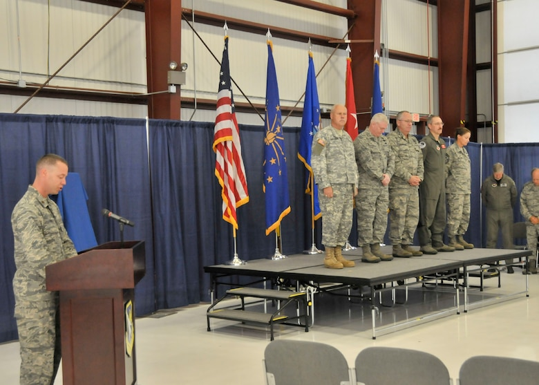 Maj. Michael Frese (left), Chaplain of the 122nd Fighter Wing, opens the wing's change of command ceremony with a prayer, Sep. 13, 2014, Fort Wayne Air National Guard Base, Fort Wayne, Indiana. Standing from left to right on stage is Maj. Gen. R. Martin Umbarger, the Adjutant General of Indiana, Brig. Gen. Jeffrey W. Hauser, Assistant Adjutant General of Indiana, Col. David L. Augustine, retiring 122FW commander, Col. Patrick R. Renwick, newly appointed 122FW Commander, and Chief Master Sgt. Christine A. Hutchins, Command Chief of the 122FW. (Air National Guard photo by Senior Airman Joseph Boals/Released)