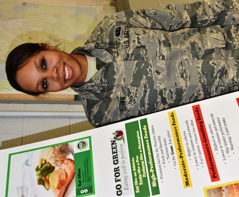 Airman 1st Class Robin Brown is the 175th Wing's March Airman Spotlight. She is a member of the 175th Force Support Squadron and is pictured with the Go For Green eating well program poster in the base dining facility. (U.S. Air National Guard photo by Senior Master Sgt. Ed Bard/RELEASED)