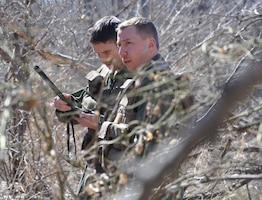 Capt. Brian Doom, 18th Air Refueling Squadron KC-135 Stratotanker pilot, and Capt. Dan Mecham, 18th ARS KC-135 pilot, attempt to radio their contact during a Survival, Evasion, Resistance, Escape training scenario at a public park in Derby, Kan., March 7, 2015.  Fifteen McConnell Reservists participated in the training during the March unit training assembly. The training was a refresher, as all Air Force aircrew go through an initial SERE training course at Fairchild AFB, Wash., during introductory training.  (U.S. Air Force photo by Tech. Sgt. Abigail Klein)