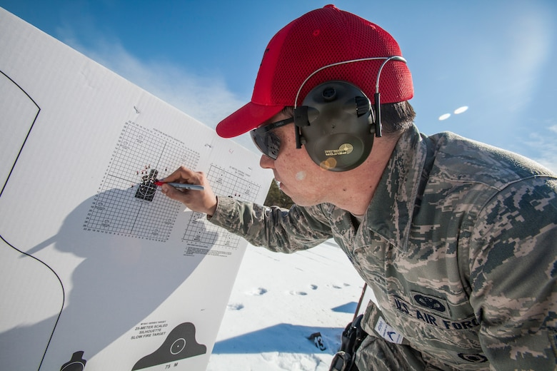 Senior Airman Raymond J. Buckno, Combat Arms Training and Maintenance, 108th Wing, New Jersey Air National Guard, examines target groupings during M4 Carbine qualification at Joint Base McGuire-Dix-Lakehurst, N.J., March 8, 2015. (U.S. Air National Guard photo by Master Sgt. Mark C. Olsen/Released)