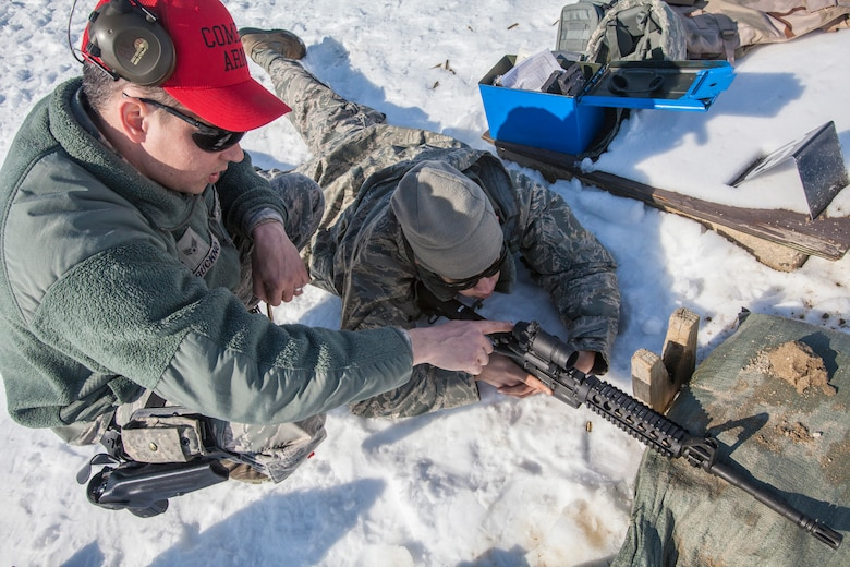 Senior Airman Raymond J. Buckno, left,  Combat Arms Training and Maintenance, helps Airman 1st Class Bryant A. Toro, both with the 108th Wing, New Jersey Air National Guard, adjust the M68 red dot sight on the M4 Carbine at Joint Base McGuire-Dix-Lakehurst, N.J., March 8, 2015. (U.S. Air National Guard photo by Master Sgt. Mark C. Olsen/Released)