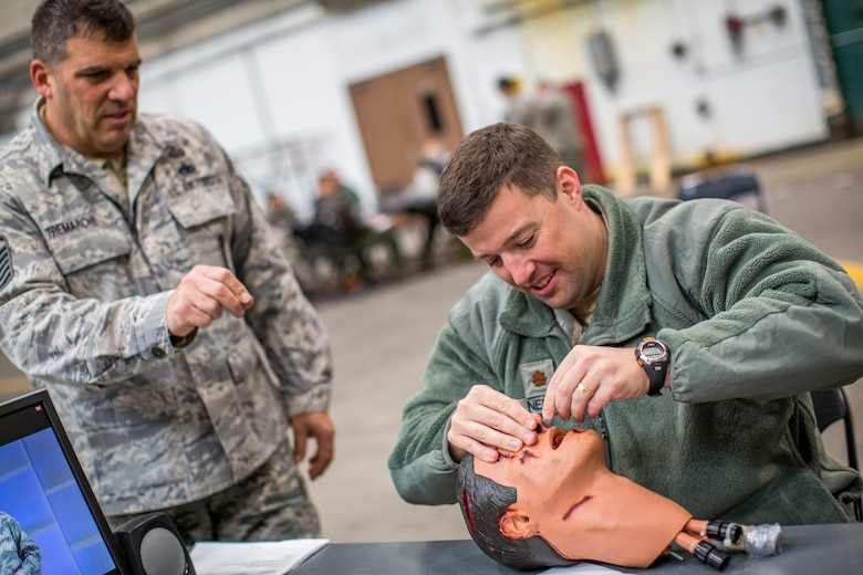 Maj. Travis Nels, 102nd Air Operations Group command and control planner, practices inserting a nasal flange in a simulated non-breathing victim with help from his training instructor, Master Sgt. Tim Tremarche, 101st Intelligence Squadron signals intelligence element supervisor, March 6, 2015 at Otis Air National Guard Base, Mass. Approximately 350 Airmen from the 102nd Intelligence Wing participated in hands-on training which covered self-aid buddy care and chemical, biological, radiological and nuclear defense. (Air National Guard photo by Staff Sgt. Jeremy Bowcock)