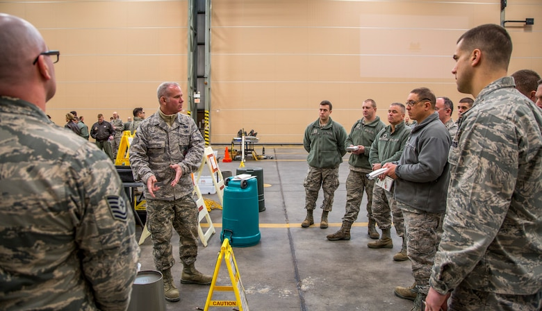 Master Sgt. Timothy Moore, 102nd Intelligence Wing emergency manager, demonstrates how to transition between contaminated zones during an expeditionary skills rodeo March 6, 2015 at Otis Air National Guard Base, Mass. Approximately 350 Airmen from the 102nd IW participated in hands-on training which covered self-aid buddy care and chemical, biological, radiological and nuclear defense. (Air National Guard photo by Staff Sgt. Jeremy Bowcock)