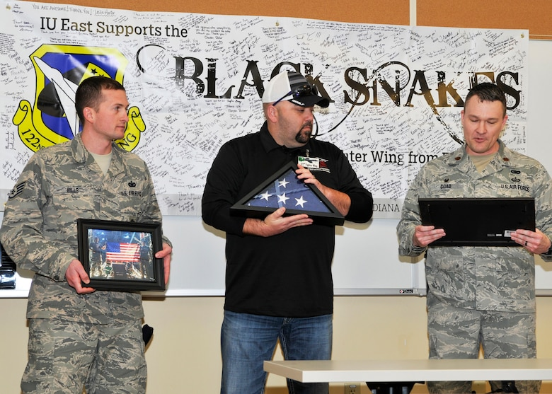 Major Charles Goad, 122nd Security Forces commander, and Staff Sgt. Marcus Bills, 122nd SFS specialist, present a support award to Darrell Johnson, President of the Indiana University East Student Veterans Organization, March 7, 2015 at the 122nd Fighter Wing Air National Guard Base, Fort Wayne, Indiana. Johnson also received a flag flown by the unit overseas. (U.S. Air Force photo by TSgt Kurt Briner)