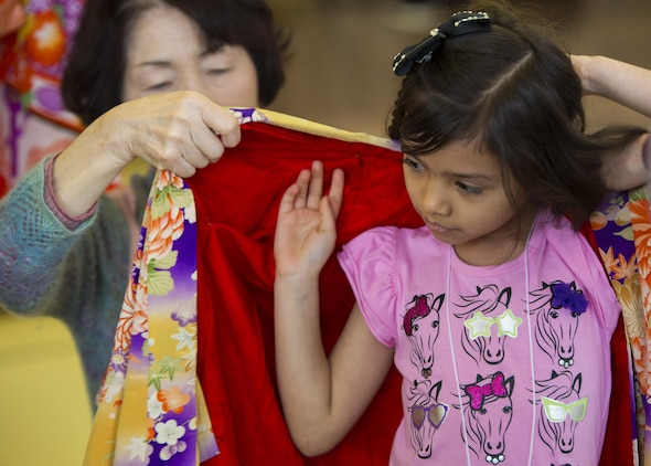 A Japanese volunteer helps a visitor from School Age Care aboard Marine Corps Air Station Iwakuni, Japan, put on a Japanese kimono during the Hina Doll Festival in Shunan City, March 7, 2015. The Hina Doll Festival, or Hinamatsuri, is a day in Japan when parents celebrate their daughters' happiness, growth and good health and is usually held on March 3.