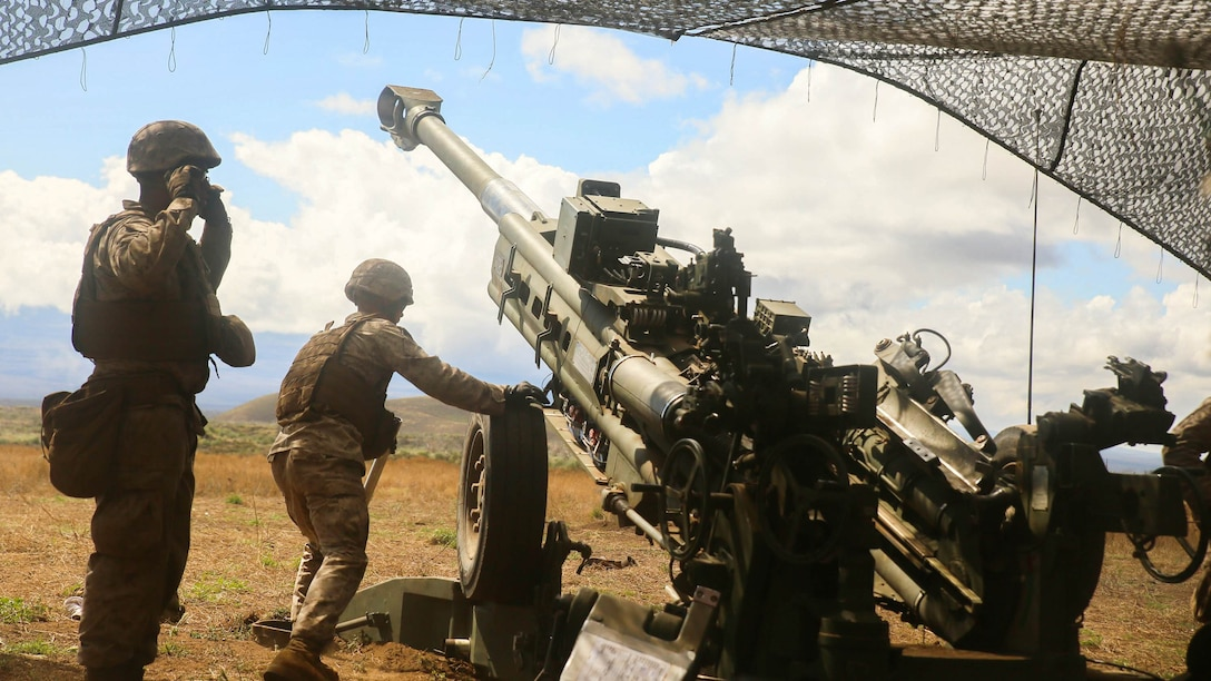 The third gun of Bravo Battery, 1st Battalion, 12th Marine Regiment fires a 155 mm howitzer under camouflage netting on Pohakuloa Training Area during Operation Spartan Fury 15.2, March 2, 2015. The training was part of Operation Spartan Fury 15.2.