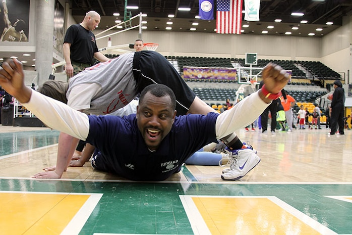 "Howard University Men's Basketball Coach Kevin Nickelberry celebrates after completing his turn at low crawling under a group of Mid-East Atlantic Conference Youth Basketball Clinic participants in ""building the house,"" March 7, 2015. Building the house is a team-building exercise where members of the team get in a modified push up position and create a tunnel while one member crawls under them and then places themselves in the modified push up position at the end as the next team member crawls under. While many of the exercise stations in the clinic focused on building basketball fundamentals and skills, the Marines station focused on building camaraderie and leadership. Nickelberry took a break from instructing shooting techniques to participate in the Marines exercises. The clinic, held at Norfolk State University, kicks off the MEAC basketball tournament and builds positive community relations with the Marines, universities and youth basketball league players in the Norfolk area. (U.S. Marine Corps photo by Sgt. Aaron Diamant/Released)"