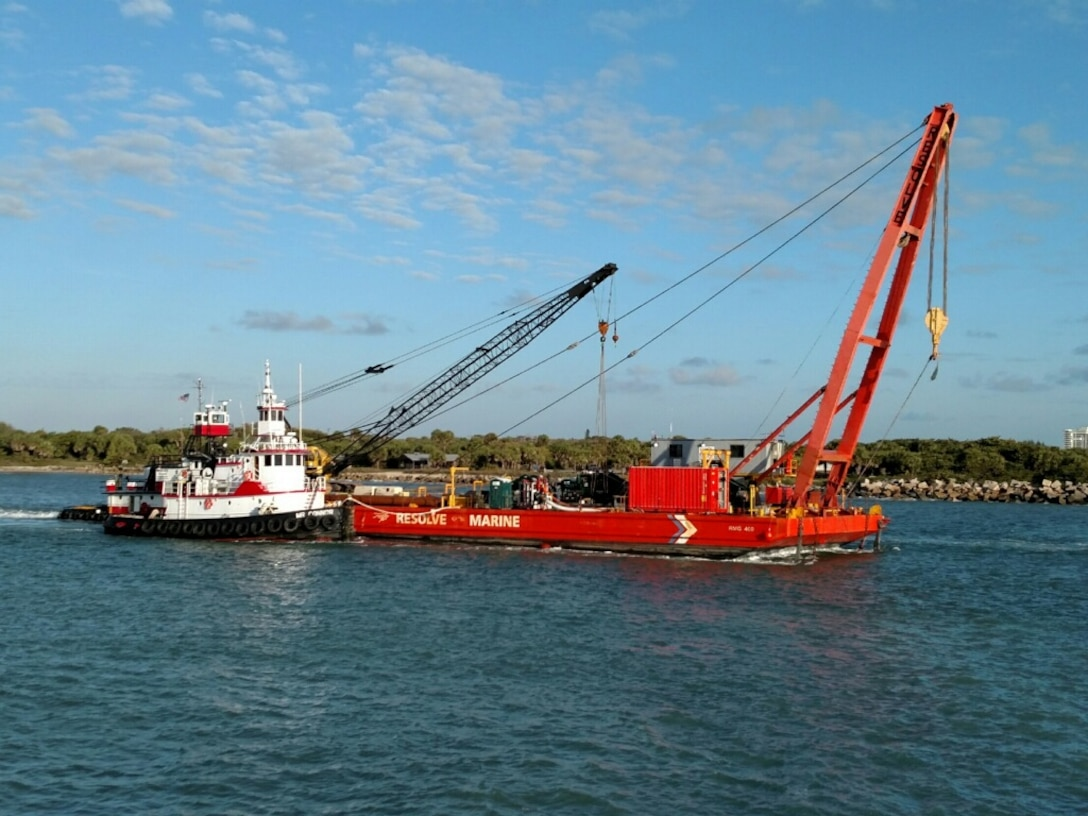 Tug boats assist the RMG-400 recovery vessel into place while wire cables are connected to four anchors.  The four-point mooring will help the recovery team maneuver at the wreck site.