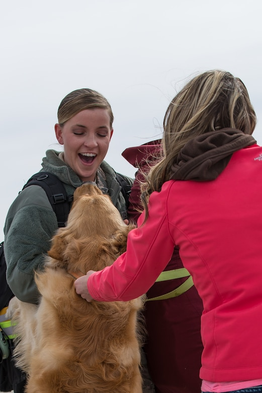 U.S. Air Force Senior Airman Hannah Richardson, pneudraulics mechanic assigned to the 153rd Airlift Wing, Wyoming Air National Guard is greeted by Kaylee Lemburg and Axel upon return from a successful deployment to Southwest Asia, Mar. 5, 2015. Richardson provided maintenance support for four C-130H Hercules aircraft which provided combat airlift of 3,140 personnel and 2,370 tons of cargo to various destinations in the region. (U.S. Air National Guard photo by Master Sgt. Charles Delano)