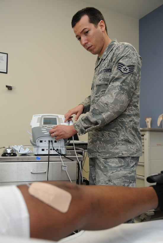 Staff Sgt. Manuel Botero, 81st Surgical Operations Squadron physical medicine technician, applies electrical stimulation to a post-operation knee surgery patient March 4, 2015, at the Keesler Medical Center, Keesler Air Force Base, Miss.  Physical and occupational therapy is offered inside the medical clinic as well as at the Levitow Training Support Facility and Matero Hall to allow students direct access to them.  (U.S. Air Force photo by Kemberly Groue)