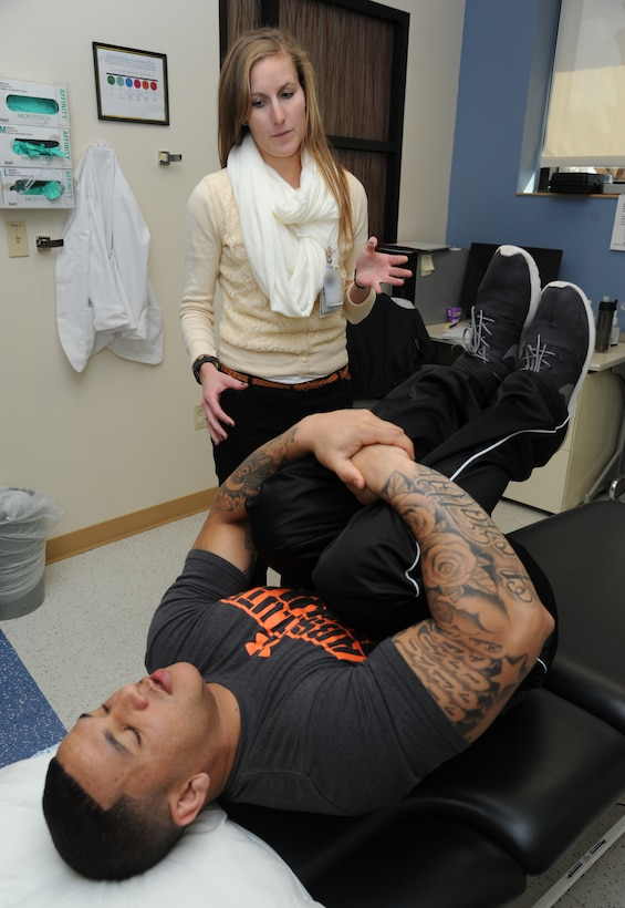 Rachel Ebmeier, Sacred Heart University student and physical therapist intern, evaluates Senior Airman John Hunt, 81st Security Forces Squadron desk sergeant, for pain level and location March 4, 2015, at the Keesler Medical Center, Keesler Air Force Base, Miss. Physical and occupational therapy is offered inside the medical clinic as well as at the Levitow Training Support Facility and Matero Hall to allow students direct access to them.  (U.S. Air Force photo by Kemberly Groue)