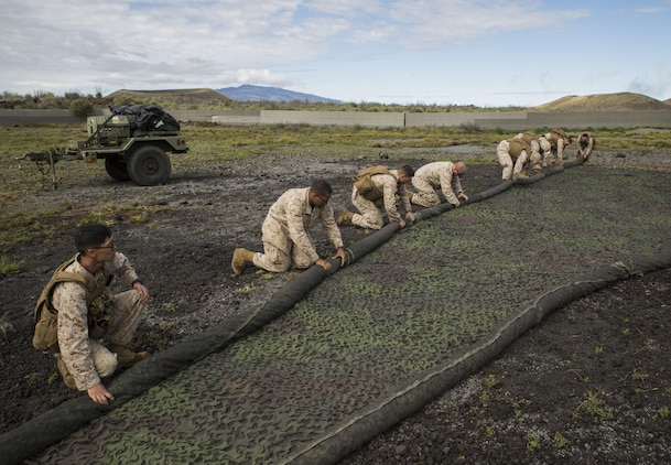 Marines work together to roll up camouflage netting, which is one of the final steps of moving a forward command element, March 5 during Dragon Fire Exercise 15-2 at Pohakuloa Training Area, Kona, Hawaii. The forward command element provides constant communication and command capabilities for the command element of an artillery unit. Marines are with Headquarters Battery, 12th Marine Regiment, 3rd Marine Division, III Marine Expeditionary Force.