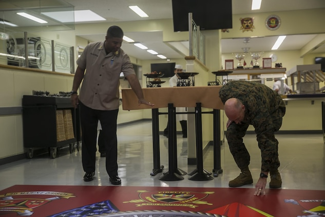 Master Sgt. Derrek L. Steele and Col. Lance A. McDaniel admire the new 12th Marine Regiment logo March 2 at Camp Hansen, Okinawa, Japan. The logo was created in honor of the chow hall being nominated for the Major General William Pendleton Thomas Hill Award. McDaniel, a native of Waco, Texas, is the commanding officer of 12th Marines, 3rd Marine Division, III Marine Expeditionary Force. Steele is the mess manager for the award winning 12th Marines Mess Hall. Steele, a native of Mt. Gilead, North Carolina is a mess manager with Headquarters Battery, 12th Marines, 3rd Marine Division, III Marine Expeditionary Force.